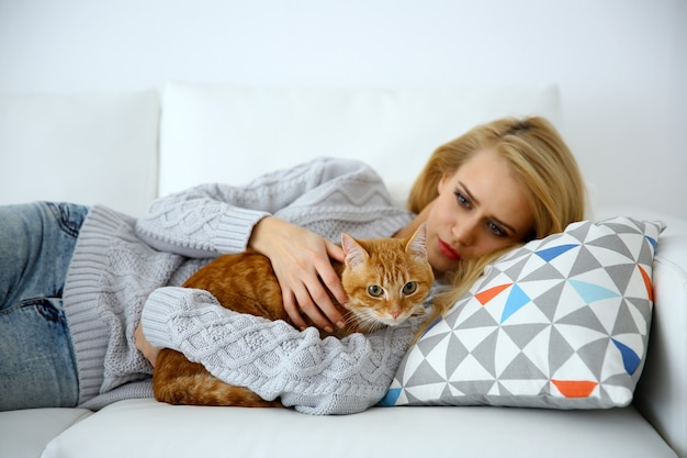 Young woman with red cat laying on sofa