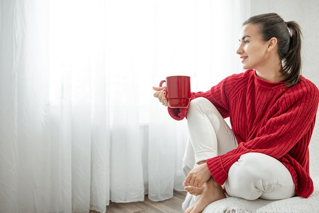 A young woman with a red cup of hot drink in a cozy red sweater is resting on the couch at home copy space.