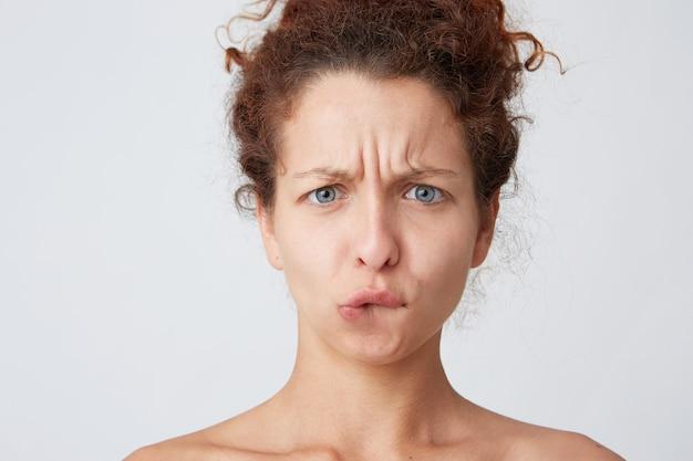 赤い巻き毛のポーズとしかめっ面を作る若い女性