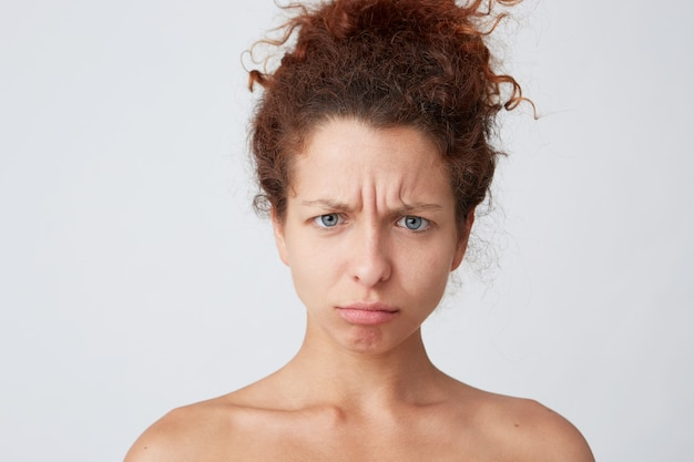 Giovane donna con capelli ricci rossi in posa e facendo smorfia
