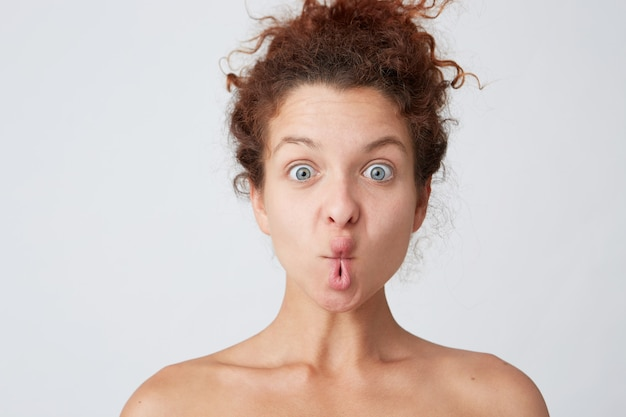 Young woman with red curly hair posing and making grimace