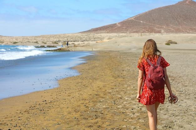 Молодая женщина с красным платьем и рюкзаком гуляет босиком по морскому пляжу