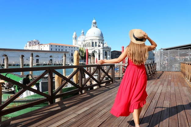 빨간 드레스와 모자를 가진 젊은 여자는 베니스, 이탈리아에서 산책