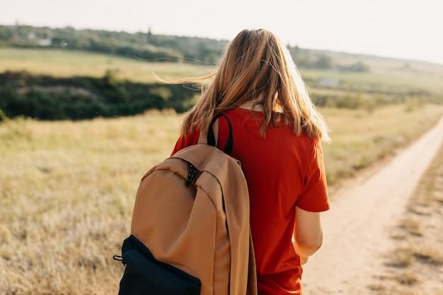 赤い髪とバックパックを持つ若い女性が離れて歩いて、後ろから撮影しました。