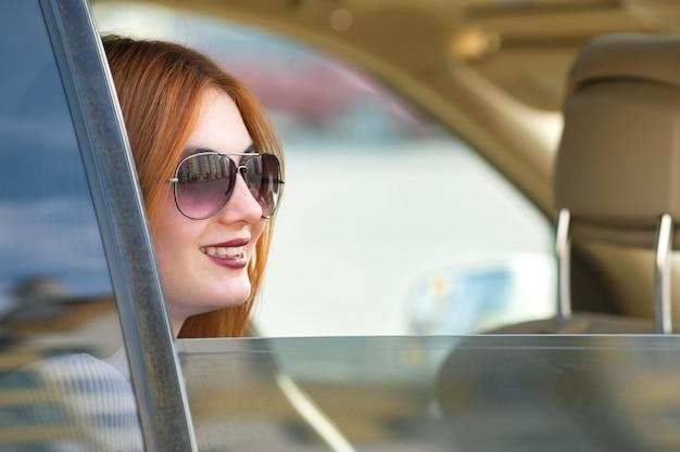 자동차로 여행하는 빨간 머리와 태양 안경을 쓴 젊은 여자.