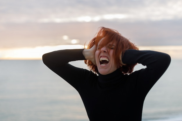 Young woman with red hair clutching her head and loudly screaming from heartache on the background of sea and sunset