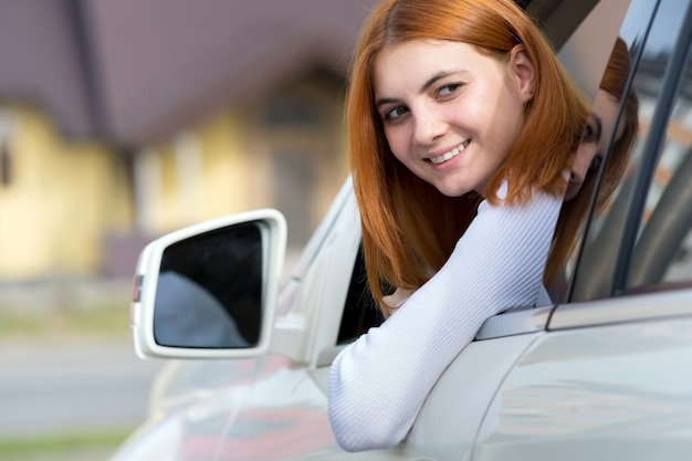 Young woman with red hair driving a car.