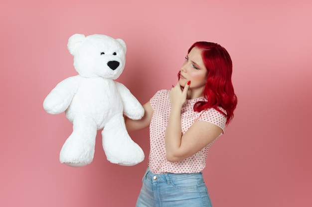 Young woman with red hair holds a large white teddy bear and rubs her chin with her hand