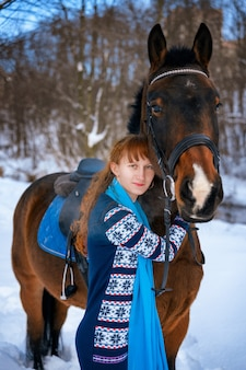 Young woman with red hair on a horse in winter