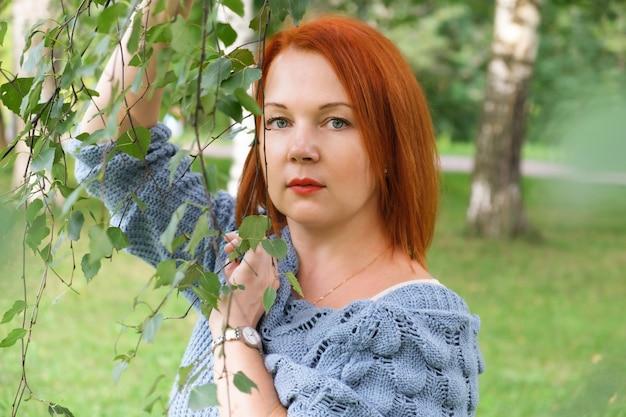 파란색 니트 스웨터를 입은 빨간 머리를 한 젊은 여성이 자작나무 옆에 서서 수심에 찬 표정을 짓고 있다