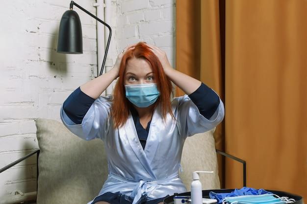 医療用マスクに赤い髪の若い女性は、covid-19の陽性検査を知ったとき、ショックで頭を抱えています。
