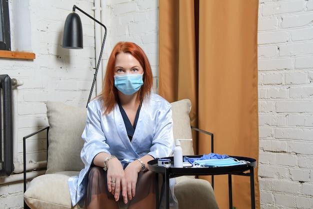 Молодая женщина с рыжими волосами в медицинской маске шокирована, узнав о положительном результате теста на covid-19