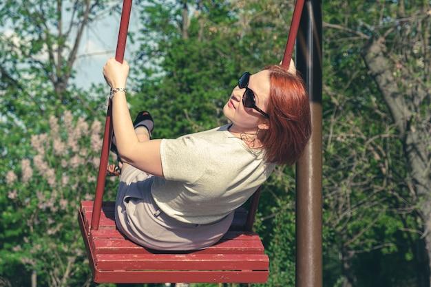 선글라스를 쓴 빨간 머리를 한 젊은 여성은 도시 공원에서 그네를 타고 미소를 짓고 있습니다. 그네를 탄 여자가 움직이면서 몸을 돌렸다. 성인을 위한 어린이 엔터테인먼트
