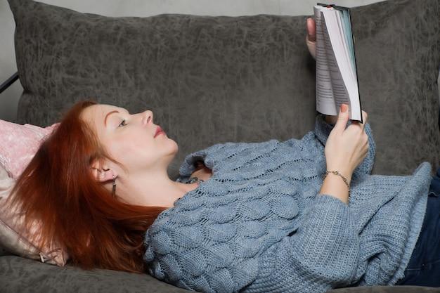 붉은 머리를 가진 젊은 여자는 소파에 누워 책을 읽고. 아늑한 인테리어의 책으로 집에서 조용한 여가를 즐기십시오. 개념 : 문학에 대한 사랑, 독학.
