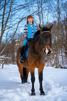 冬の馬に赤い髪を持つ若い女