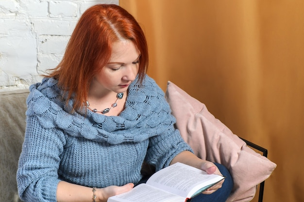 붉은 머리를 가진 젊은 여자는 흰색 벽돌 벽과 금 커튼의 배경에 로프트의 내부에 아늑한 안락의 자에 책을 읽습니다.