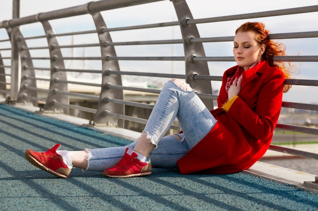 A young woman with red hair in a red coat and red sneakers is sitting on a bridge on a sunny