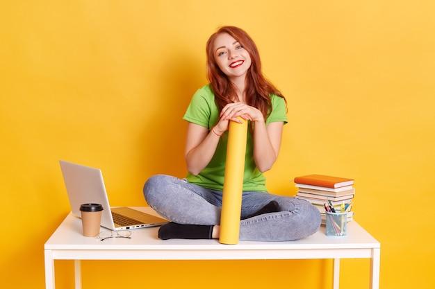 スパイグラスを持って、足を組んで白い机の上に座っている赤い髪の若い女性