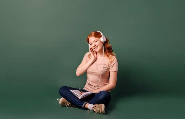 A young woman with red hair sitting reads a book and listens to music