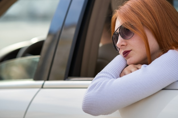 Young woman with red hair and sun glasses travelling by car. passenger looking out of the rear window of a taxi in a city.