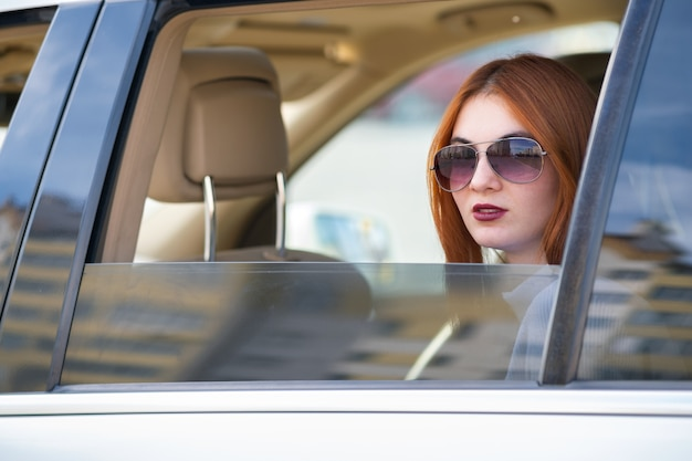 Young woman with red hair and sun glasses travelling by car.
