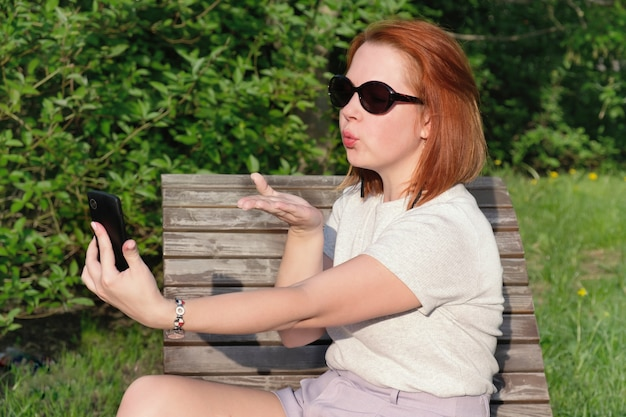 Young woman with red hair in sunglasses blows a kiss at the screen of his smartphone on his outstretched hand to take a photo of herself on phone. woman makes a selfie on a smartphone in a city park.