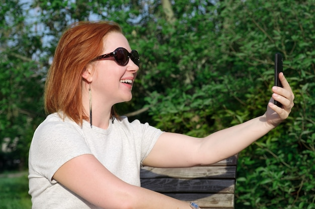Young woman with red hair in sunglasses smiles at the screen of his smartphone on his outstretched hand to take a photo of herself on the phone. woman makes a selfie on a smartphone in a city park.