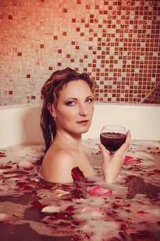 Young woman with red hair take bubble bath with candle.