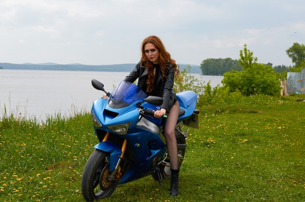 A young woman with red hair and wearing a black leather jacket on a blue sports motorcycle