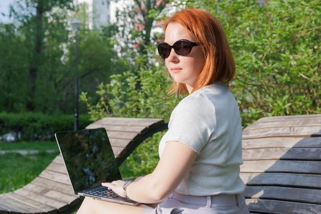 공원 벤치에 노트북과 빨간 머리를 가진 젊은 여자. 프리랜서 여성은 공원에서 일합니다. 뒤에서 촬영한 여성은 몸을 돌렸다.