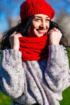 晴れた冬の日に公園で赤い帽子とスカーフを持つ若い女性