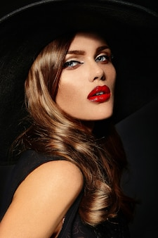 Young woman with red lips and black hat