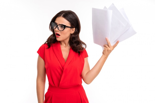 A young woman with red lips, bright makeup, dark wavy long hair, in a red suit, black glasses with transparent stacks stands, holds papers and is surprised