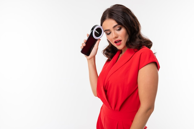 A young woman with red lips, bright makeup, dark wavy long hair, in a red suit, black glasses with transparent stacks stands and holds the phone in her hands