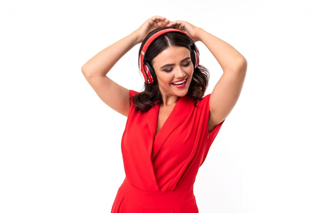 A young woman with red lips, bright makeup, dark wavy long hair, in a red suit, black glasses with transparent stacks stands and listens to music in headphones and dances
