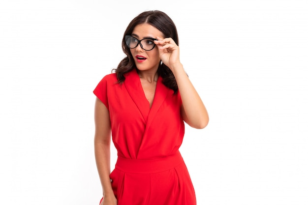 A young woman with red lips, bright makeup, dark wavy long hair, in a red suit, black glasses with transparent stacks stands