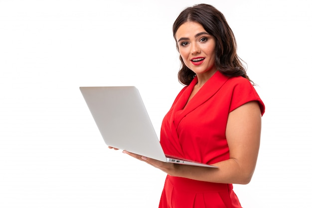 A young woman with red lips, bright makeup, dark wavy long hair, in a red suit, stands with a white laptop