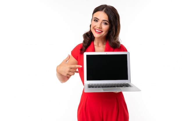A young woman with red lips, bright makeup, works with a white laptop and shows something on screen, picture isolated