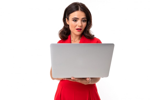A young woman with red lips, bright makeup, works with a white laptop