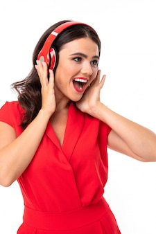 A young woman with red lips listens to music in headphones and smiles