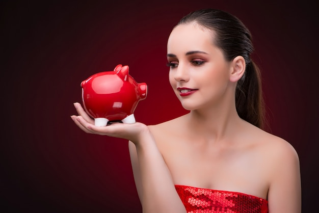 Young woman with red piggybank