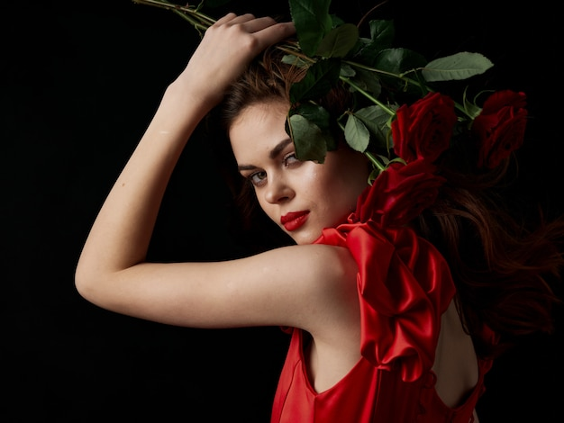 Young woman with red roses in her hands in a red dress