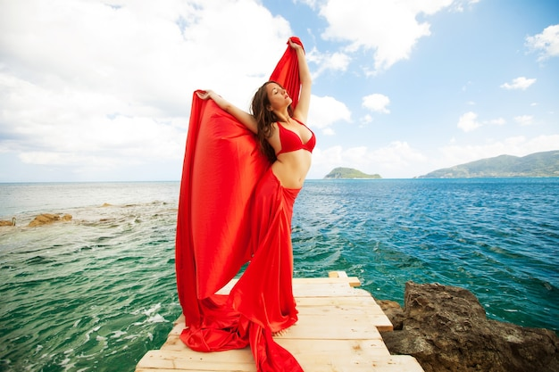 Young woman with red skirt and  fabric like a wings. vogue style.