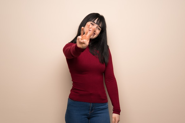 Young woman with red turtleneck happy and counting three with fingers