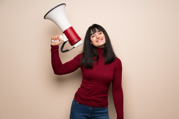 Young woman with red turtleneck holding a megaphone