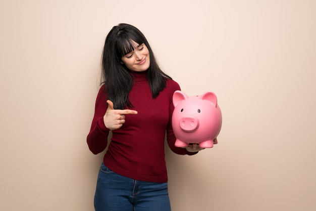 Young woman with red turtleneck holding a piggybank