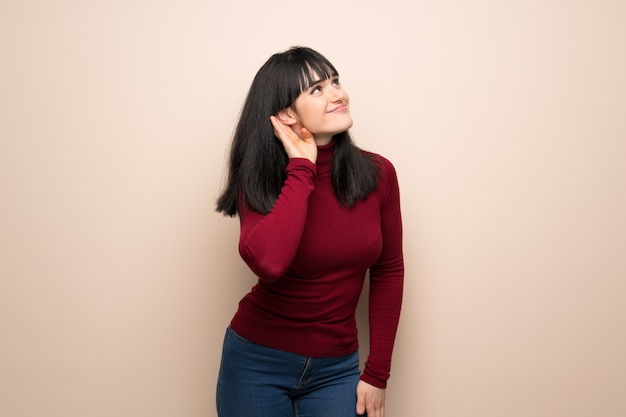 Young woman with red turtleneck listening to something by putting hand on the ear