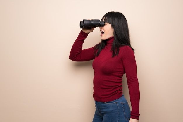 Young woman with red turtleneck and looking in the distance with binoculars