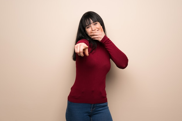Young woman with red turtleneck pointing with finger at someone and laughing