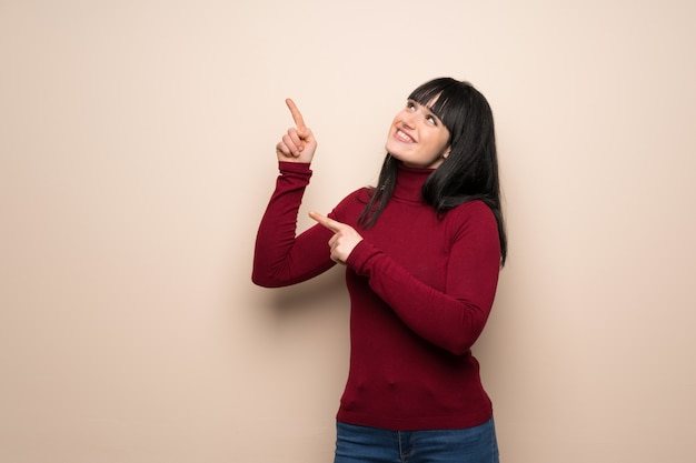 Young woman with red turtleneck pointing with the index finger and looking up